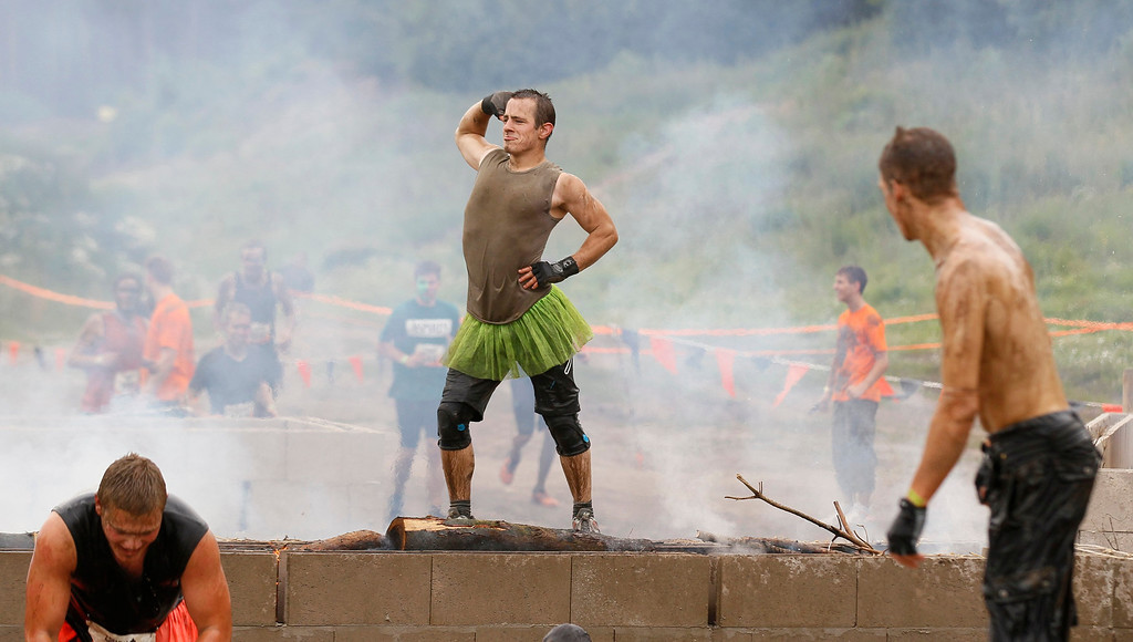 """. A participant of the \""""Tough Mudder\"""" endurance event series poses on top of an open fire at the \""""Fire Walker\"""" obstacle in the Fursten Forest, a former British Army training ground near the north-western German city of Osnabrueck July 13, 2013. The hardcore but un-timed event over 16 km (10 miles) was designed by British Special Forces to test mental as well as physical strength. Some 4,000 competitors had to overcome obstacles of common human fears, such as fire, water, electricity and heights.   REUTERS/Wolfgang Rattay"""