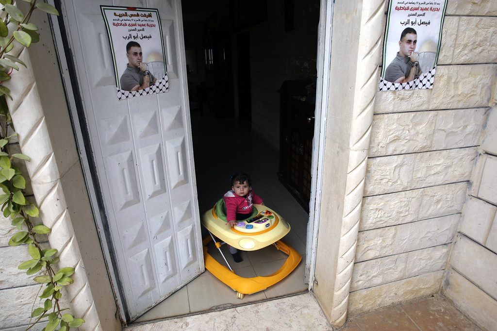 """. A child of a Palestinian relative of Faisal Abo Al-Rob plays at the doorway of their home where Abo Al-Rob\'s posters hang in the West Bank village of Kabatyeh near Jenin city, Sunday, Dec. 29, 2013. Abo Al-Rob is one of the 26 Palestinian prisoners who were convicted in connection to the killing of Israelis, that Israel announced to release this week. The Arabic on the posters reads: \""""The freedom Sun rose for releasing Dean of Kabatyeh prisoners, Faisal Abo Al-Rob.\"""" (AP Photo/Mohammed Ballas)"""