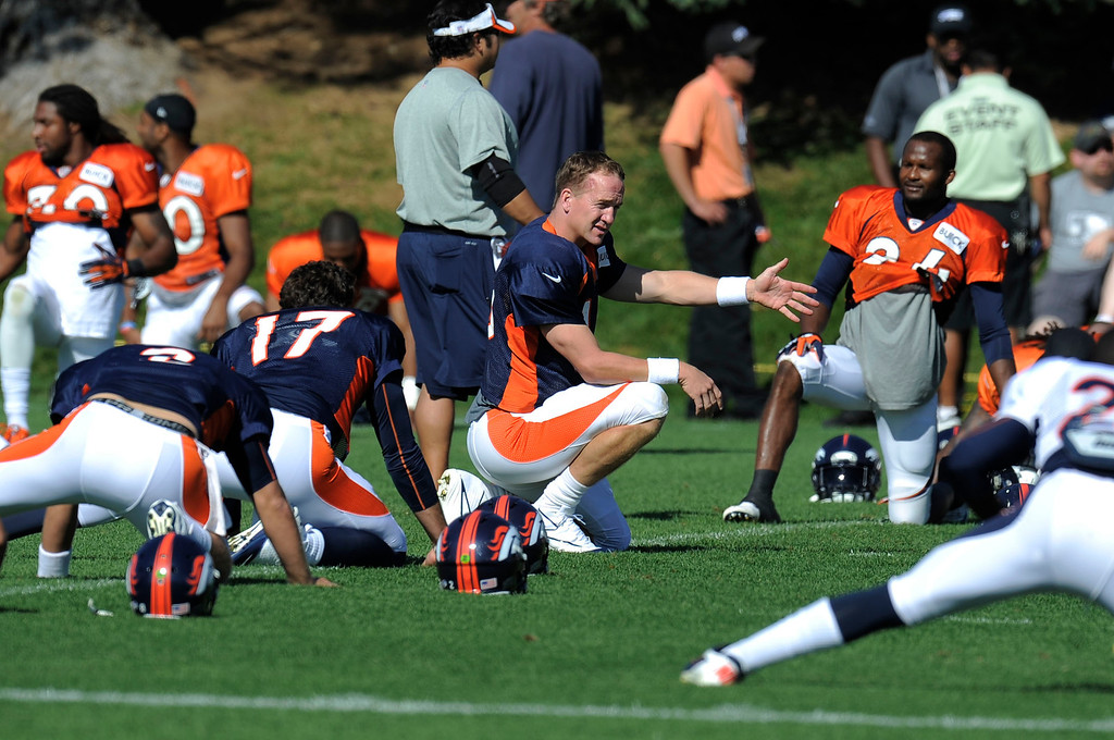 . Denver Broncos QB Peyton Manning (18) stretches during training camp August 13, 2013 at Dove Valley. (Photo By John Leyba/The Denver Post)