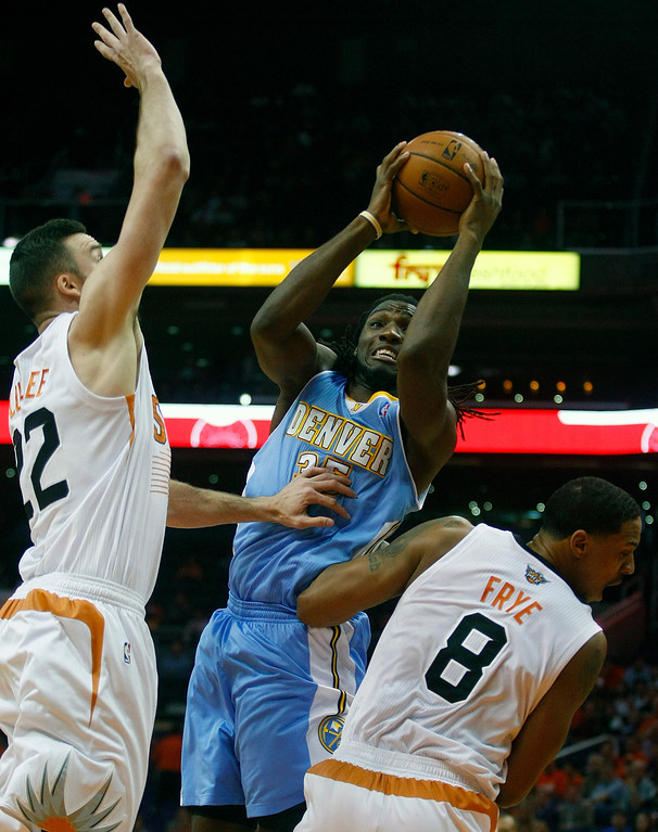 . Denver Nuggets power forward Kenneth Faried (35) shoots between Phoenix Suns center Miles Plumlee (22) and Channing Frye (8) in the first quarter during an NBA basketball game on Friday, Nov. 8, 2013, in Phoenix. (AP Photo/Rick Scuteri)