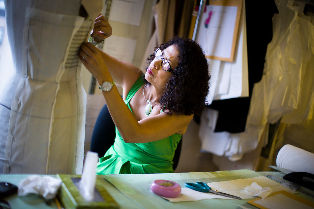 . Pattern maker Luz Pyne pins cloth to a mannequin at the New York studio of fashion designer Carmen Marc Valvo.  Valvo will show his Spring 2014 collection on Sept. 6 at Lincoln Center in New York. (AP Photo/John Minchillo)