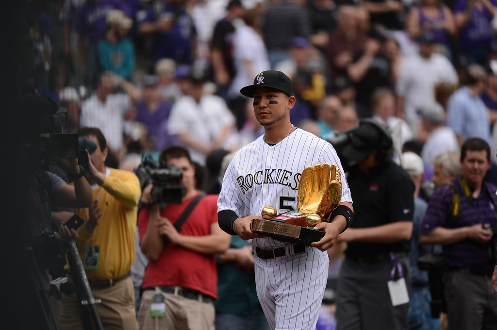 . Carlos Gonzalez (5) of the Colorado Rockies carries his National League Rawlings Gold Glove Award off the field before the start of the game.  (Photo by Hyoung Chang/The Denver Post)