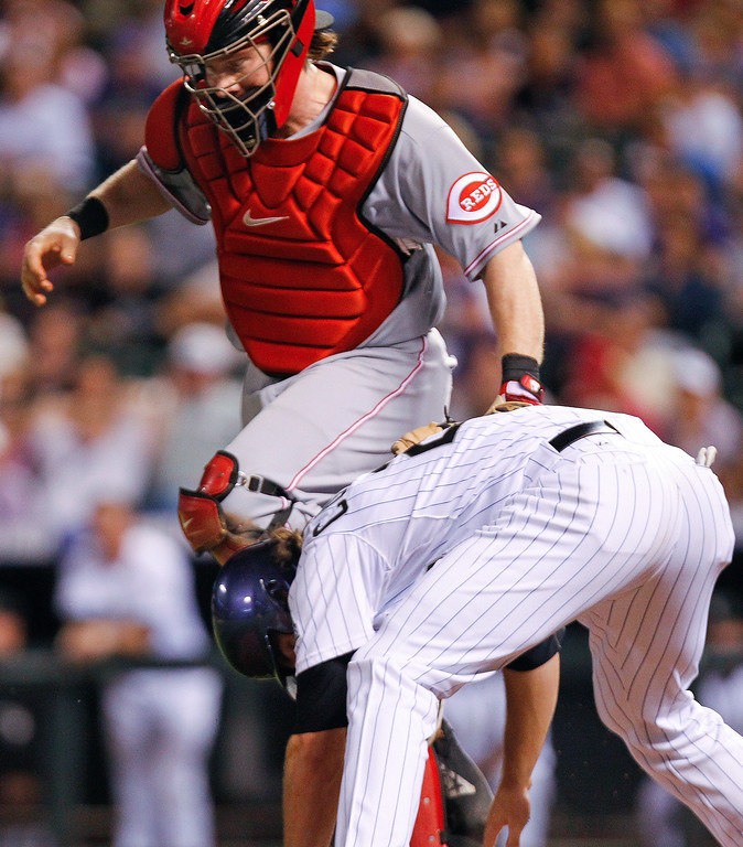 . Cincinnati Reds\' Ryan Hanigan, top, tags out Colorado Rockies\' Charlie Culberson, bottom, when he got caught between third and home during the fourth inning of a baseball game, Friday, Aug. 30, 2013, in Denver. (AP Photo/Barry Gutierrez)