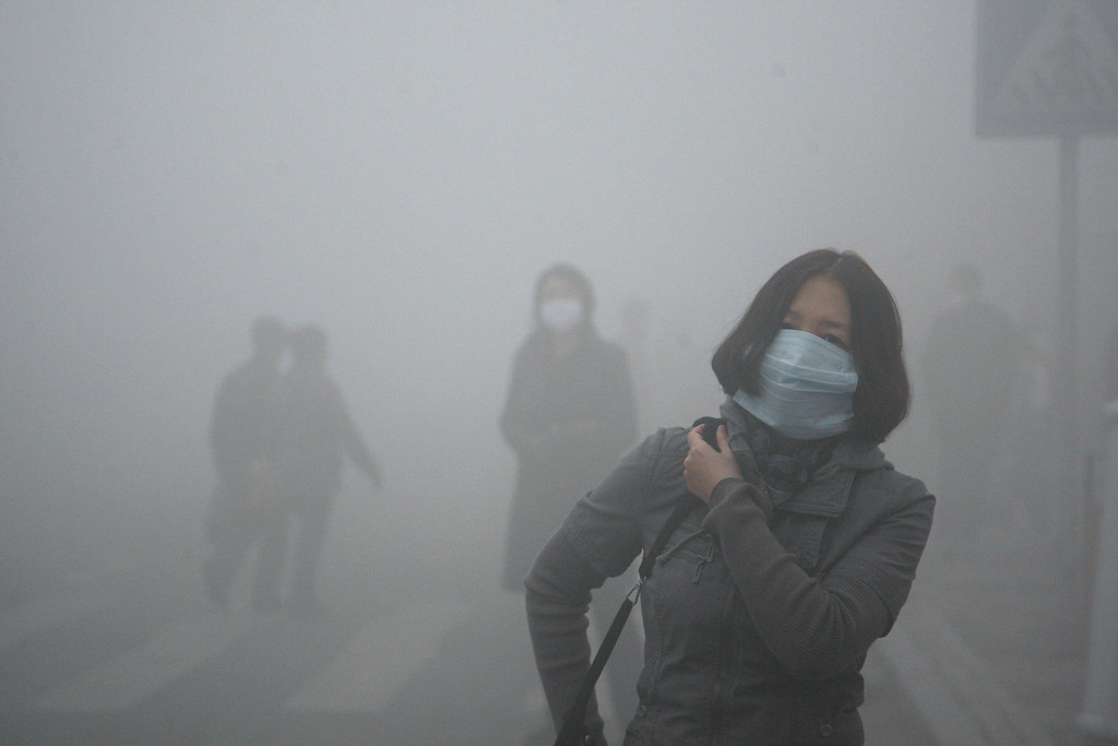 . A woman wearing a mask walk through a street covered by dense smog in Harbin, northern China, Monday, Oct. 21, 2013. (AP Photo/Kyodo News)
