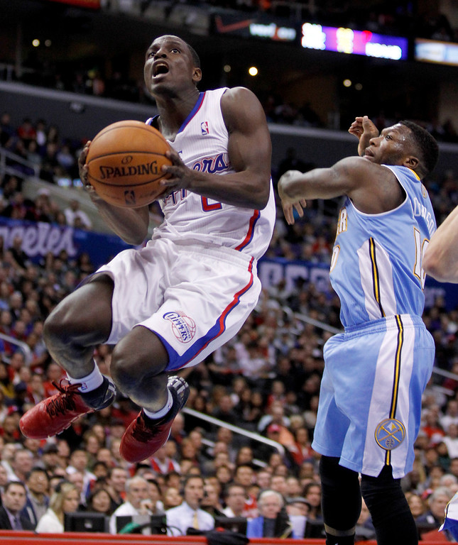 . Los Angeles Clippers guard Darren Collison, left, gets past Denver Nuggets guard Nate Robinson on the way to the basket during the first half of an NBA basketball game in Los Angeles on Saturday, Dec. 21, 2013. (AP Photo/Alex Gallardo)
