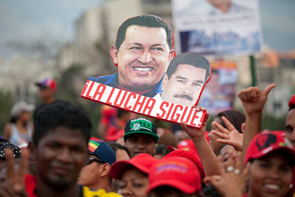 """. A supporter holds up a sign that reads in Spanish \""""The fight continues\"""" and shows late President Hugo Chavez, left, and current presidential candidate Nicolas Maduro, before the closing campaign rally for Maduro in Caracas, Venezuela, Thursday, April 11, 2013. Maduro, Chavez\'s hand-picked successor, is running for president against opposition candidate Henrique Capriles on April 14. (AP Photo/Ramon Espinosa)"""
