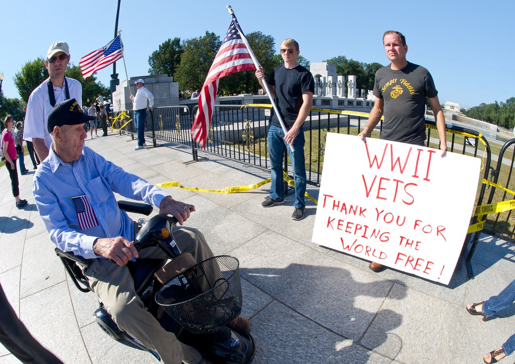 . US military veteran Eugene Morgan(wheelchair) and his son Jeff, are greeted by supporters Lance Frye(R) and Jeff Lee as he makes his first visit to the World War II Memorial October 2, 2013 in Washington, DC. Veterans groups continue to visit the various war memorials even though they have been shuttered by the government shutdown.  AFP PHOTO / Karen BLEIER/AFP/Getty Images