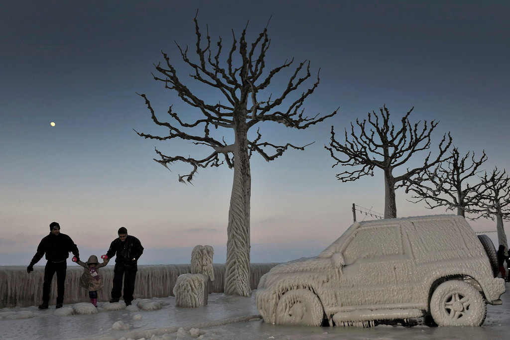 . In this Feb. 5, 2012 file photo, people walk along an icy promenade past ice covered cars and trees on the shores of Lake Geneva in Versoix, Switzerland. Across Eastern Europe, thousands of people dug out from heavy snow that had fallen during a cold snap and killed hundreds of people.  (AP Photo/Keystone/Martial Trezzini, File)