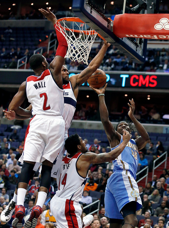 . Washington Wizards guard John Wall (2), forward Trevor Booker and guard Glen Rice Jr. (14) combine to block a shot by Denver Nuggets forward Kenneth Faried (35) in the first half of an NBA basketball game on Monday, Dec. 9, 2013, in Washington. (AP Photo/Alex Brandon)