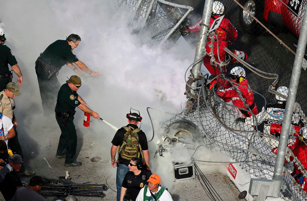 . Rescue workers respond as an engine burns after going through the catch fence following a last-lap incident during the NASCAR Nationwide Series DRIVE4COPD 300 race at the Daytona International Speedway in Daytona Beach, Florida February 23, 2013. The Daytona 500 NASCAR Sprint Cup race is scheduled for February 24.         REUTERS/Pierre Ducharme