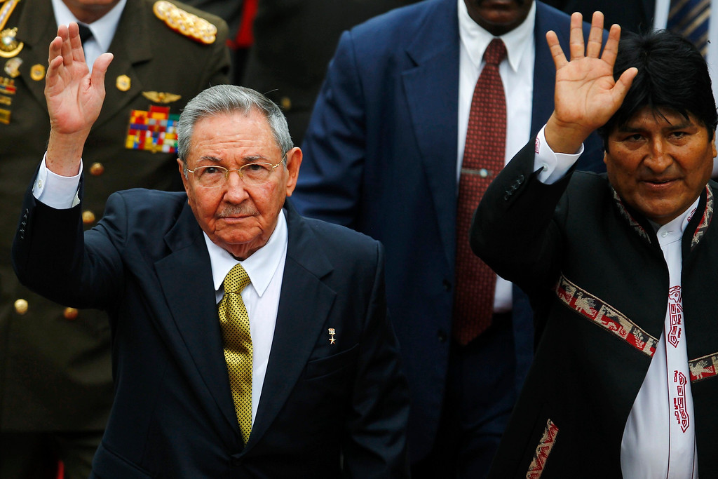 . Cuba\'s President Raul Castro (L) and Bolivia\'s President Evo Morales wave to supporters during a ceremony to swear Venezuela\'s President Nicolas Maduro (not pictured) into office, in Caracas April 19, 2013. Maduro was sworn in as Venezuela\'s president on Friday at a ceremony attended by several Latin American leaders, after a decision to widen an electronic audit of the vote took some of the heat out of a dispute over his election. REUTERS/Carlos Garcia Rawlins