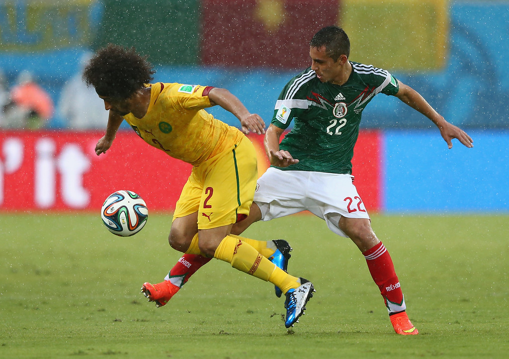 . Benoit Assou-Ekotto of Cameroon and Paul Aguilar of Mexico battle for the ball during the 2014 FIFA World Cup Brazil Group A match between Mexico and Cameroon at Estadio das Dunas on June 13, 2014 in Natal, Brazil.  (Photo by Jamie Squire/Getty Images)