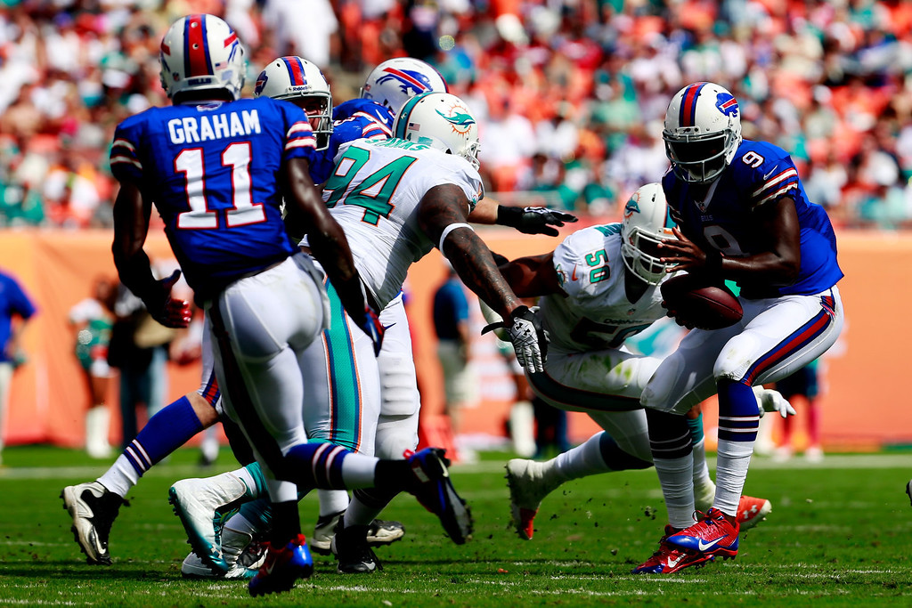 . Quarterback Thad Lewis #9 of the Buffalo Bills is pressured by  Randy Starks #94 of the Miami Dolphins and Olivier Vernon #50 of the Miami Dolphins at Sun Life Stadium on October 20, 2013 in Miami Gardens, Florida.  (Photo by Chris Trotman/Getty Images)