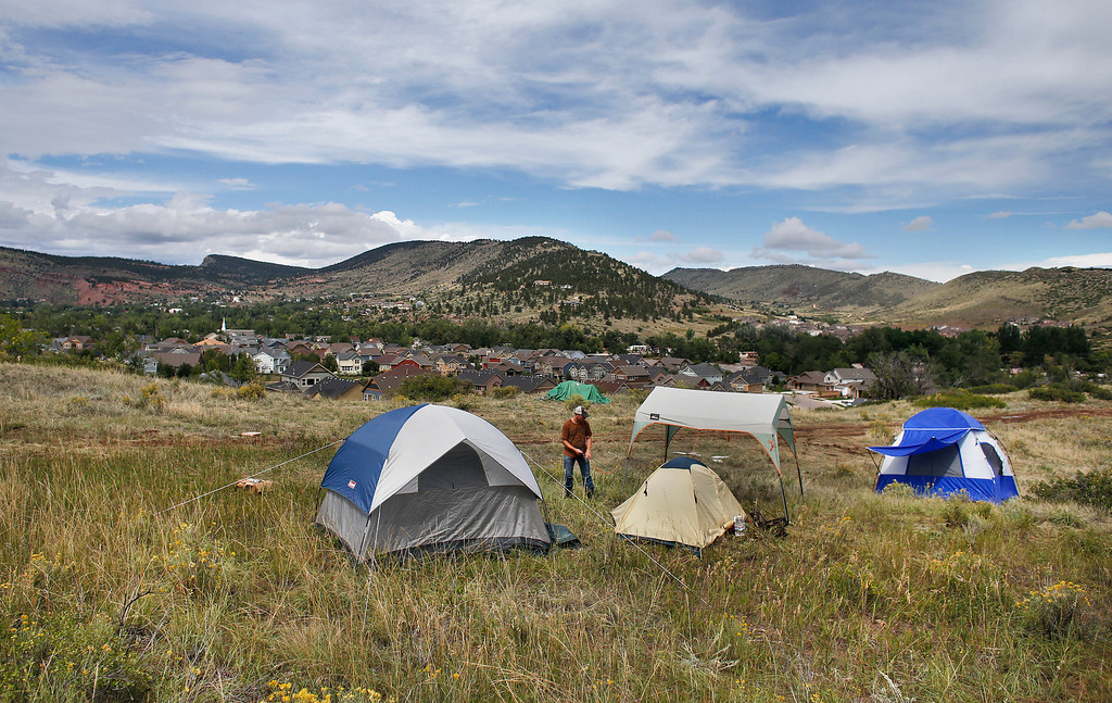 . Temporarily displaced Lyons resident Kevin Bonner walks among a makeshift camp for people who voluntarily camped on higher ground due to fears of a dam breaking, on a hill overlooking Lyons, Colo., Friday Sept. 13, 2013.  (AP Photo/Brennan Linsley)