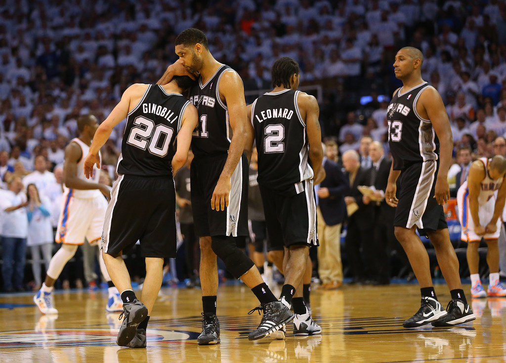 . OKLAHOMA CITY, OK - MAY 31:  Tim Duncan #21 of the San Antonio Spurs hugs teammate Manu Ginobili #20 after Ginobili hit a three-point shot against the Oklahoma City Thunder in the second half during Game Six of the Western Conference Finals of the 2014 NBA Playoffs at Chesapeake Energy Arena on May 31, 2014 in Oklahoma City, Oklahoma. (Photo by Ronald Martinez/Getty Images)
