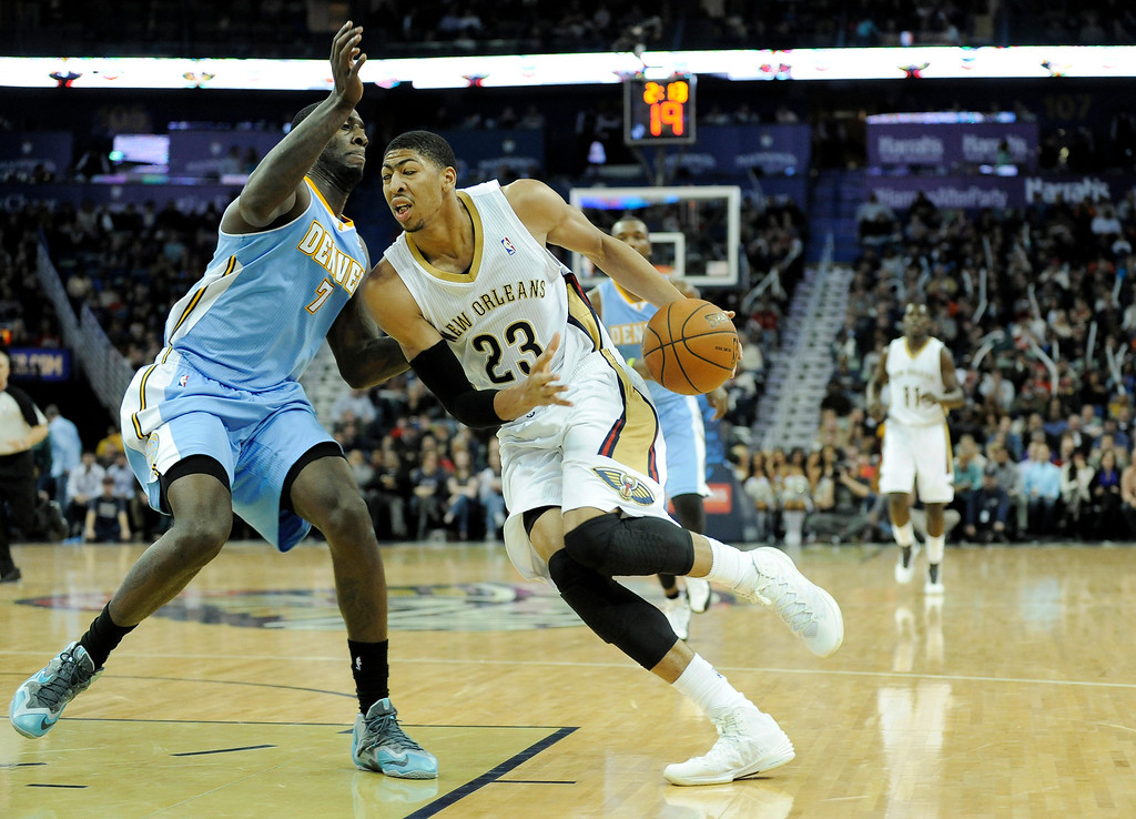 . New Orleans Pelicans center Anthony Davis (23) drives past Denver Nuggets forward J.J. Hickson (7) in the second half of an NBA basketball game in New Orleans, Friday, Dec. 27, 2013. New Orleans won 105-89. (AP Photo/Stacy Revere)