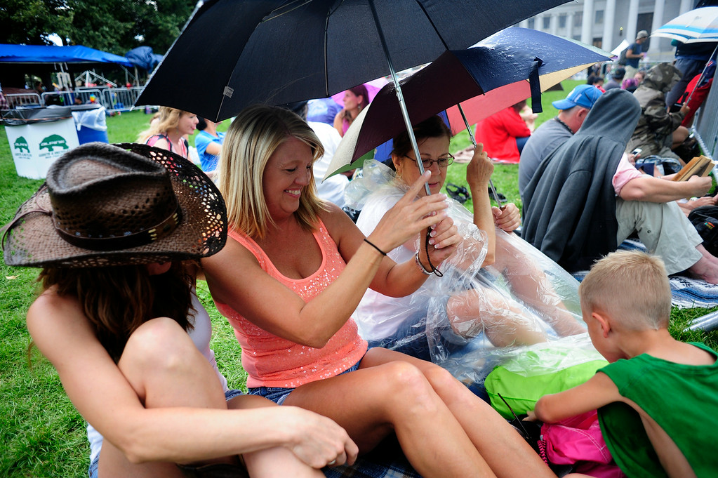 . From left, Deanna Strappelli, Rene Mattek, Linda Baker, and Jack Ladewig, 6, shelter from the rain while holding their front row spot for The Wallflowers to perform, during the A Taste of Colorado festival at Civic Center Park in Denver, Colorado Saturday,  August 30, 2014. (Photo By Brenden Neville / Special to The Denver Post)