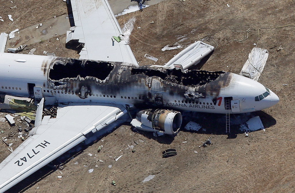 . A Boeing 777 airplane lies burned near the runway after it crash-landed at San Francisco International Airport July 6, 2013 in San Francisco, California. An Asiana Airlines passenger aircraft coming from Seoul, South Korea crashed while landing, killing two people and injuring scores of others.  (Photo by Ezra Shaw/Getty Images)