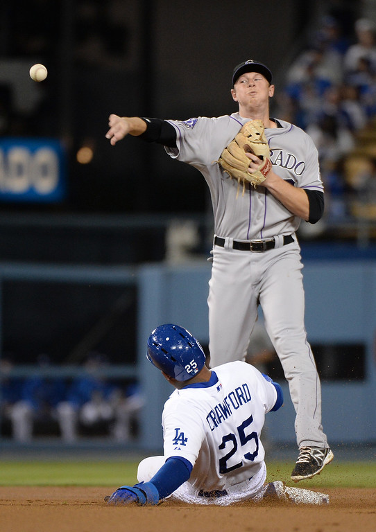 . LOS ANGELES, CA - SEPTEMBER 27:  DJ LeMahieu #9 of the Colorado Rockies throws to first after a force out of Carl Crawford #25 of the Los Angeles Dodgers during the first inning at Dodger Stadium on September 27, 2013 in Los Angeles, California.  (Photo by Harry How/Getty Images)