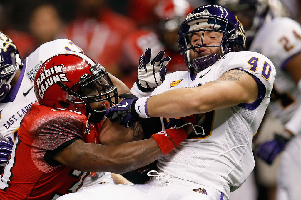 . Tyler Morvant #39 of the Louisiana-Lafayette Ragin Cajuns tackles Hunter Furr #40 of the East Carolina Pirates during the R+L Carriers New Orleans Bow at the Mercedes-Benz Superdome on December 22, 2012 in New Orleans, Louisiana.  (Photo by Chris Graythen/Getty Images)