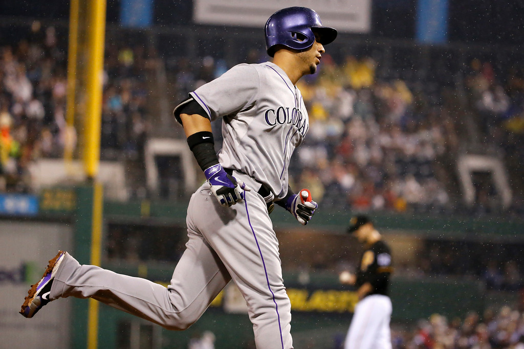 . Colorado Rockies\' Carlos Gonzalez, left rounds third after hitting a two run home run off Pittsburgh Pirates starting pitcher Charlie Morton, right rear, during the seventh inning of a baseball game in Pittsburgh Saturday, July 19, 2014. (AP Photo/Gene J. Puskar)