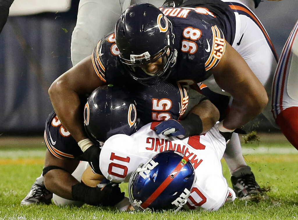 . New York Giants quarterback Eli Manning (10) gets sacked by Chicago Bears linebacker Lance Briggs (55) and defensive end Corey Wootton (98) in the second half of an NFL football game, Thursday, Oct. 10, 2013, in Chicago. (AP Photo/Nam Y. Huh)