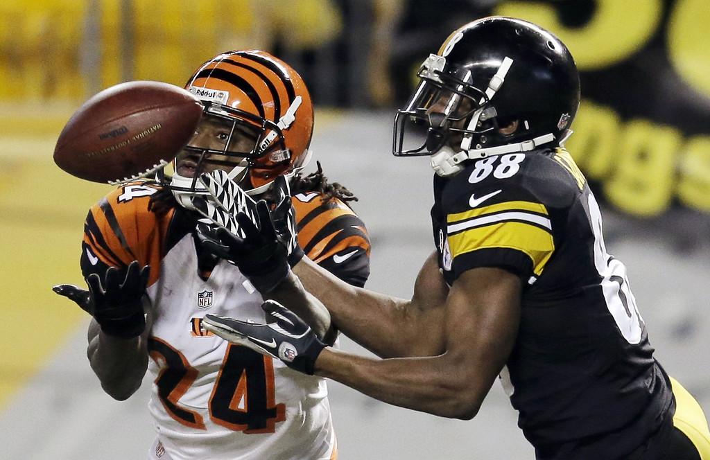 . Cincinnati Bengals cornerback Adam Jones (24) intercepts a pass intended for Pittsburgh Steelers wide receiver Emmanuel Sanders (88) in the third quarter of an NFL football game in Pittsburgh, Sunday, Dec. 15, 2013. (AP Photo/Gene J. Puskar)