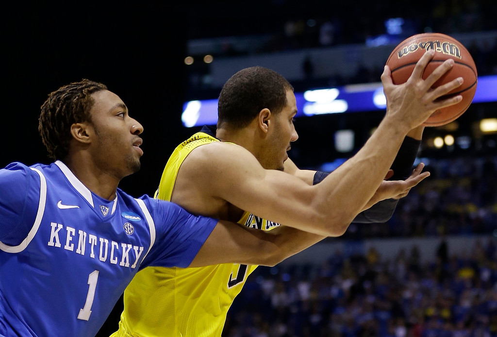 . Kentucky\'s James Young, left, knocks the ball away from Michigan\'s Jordan Morgan during the first half of an NCAA Midwest Regional final college basketball tournament game Sunday, March 30, 2014, in Indianapolis. (AP Photo/David J. Phillip)