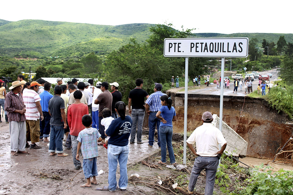 . Residents stare at a bridge swept away by heavy rains in Chilpancingo, state of Guerrero, Mexico, on September 17, 2013. Mexican authorities scrambled Tuesday to launch an air lift to evacuate tens of thousands of tourists stranded amid floods in the resort of Acapulco following a pair of deadly storms. The official death toll rose to 47 after the tropical storms, Ingrid and Manuel, swarmed large swaths of the country during a three-day holiday weekend, sparking landslides and causing rivers to overflow in several states. EDUARDO GUERRERO/AFP/Getty Images