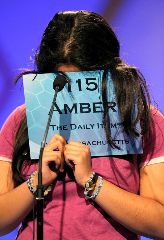 """. Amber Born, 14 of Marblehead, Mass., covers her face while spelling \""""malacophilous\"""" during the semifinal round of the Scripps National Spelling Bee in Oxon Hill, Md., Thursday, May 30, 2013. (AP Photo/Cliff Owen)"""