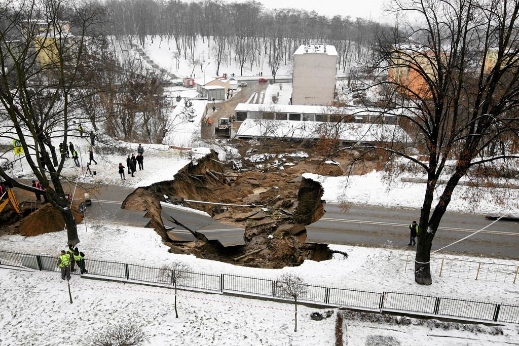 . Onlookers examine the damage after a section of a road collapsed in Ostrowiec Swietokrzyski, southern Poland December 19, 2012. A hole, measuring 10 meters (33 ft) deep and at least 50 metres (164 ft) wide, appeared on a road in Ostrowiec Swietokrzyski over Tuesday night, reported by local media. REUTERS/Pawel Malecki/Agencja Gazeta