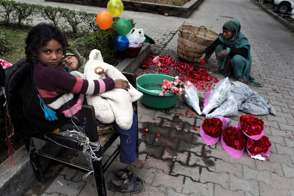 . Zahra, 8, carries her niece while her sister prepares flowers to sell on Valentine\'s Day in Islamabad February 14, 2013. REUTERS/Zohra Bensemra