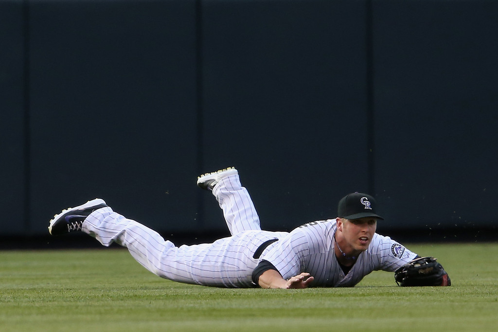 . DENVER, CO - MAY 02:  Left fielder Corey Dickerson #6 of the Colorado Rockies makes a diving catch on a line drive by Chris Young #1 of the New York Mets in the first inning at Coors Field on May 2, 2014 in Denver, Colorado.  (Photo by Doug Pensinger/Getty Images)