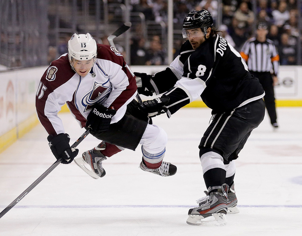 . Los Angeles Kings defenseman Drew Doughty, right, checks Colorado Avalanche right wing P.A. Parenteau during the second period of an NHL hockey game, Saturday, Dec. 21, 2013, in Los Angeles. (AP Photo/Chris Carlson)