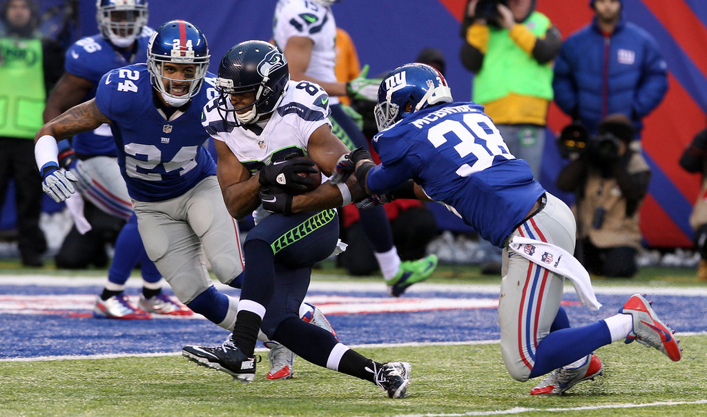 . Seattle Seahawks wide receiver Doug Baldwin, center, pushes through the tackle-attempts of New York Giants cornerbacks Terrell Thomas (24) and Trumaine McBride (38) while scoring on a touchdown pass from quarterback Russell Wilson during the second half of an NFL football game on Sunday, Dec. 15, 2013, in East Rutherford, N.J. (AP Photo/Peter Morgan)