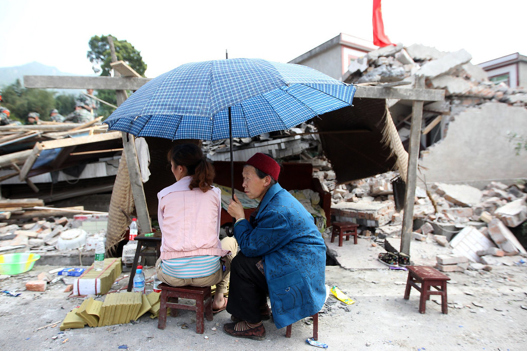 . A girl gives offerings to the dead by the side of a badly damaged building in Longmen township, an area close to the epicenter of a shallow 7.0 magnitude earthquake that hit the city of Ya\'an, southwest China\'s Sichuan province on April 20, 2013. More than 100 people were killed and 3,000 injured when a strong earthquake shook southwest China on April 20, wrecking homes and triggering landslides in an area devastated by a major tremor in 2008. AFP PHOTOSTR/AFP/Getty Images