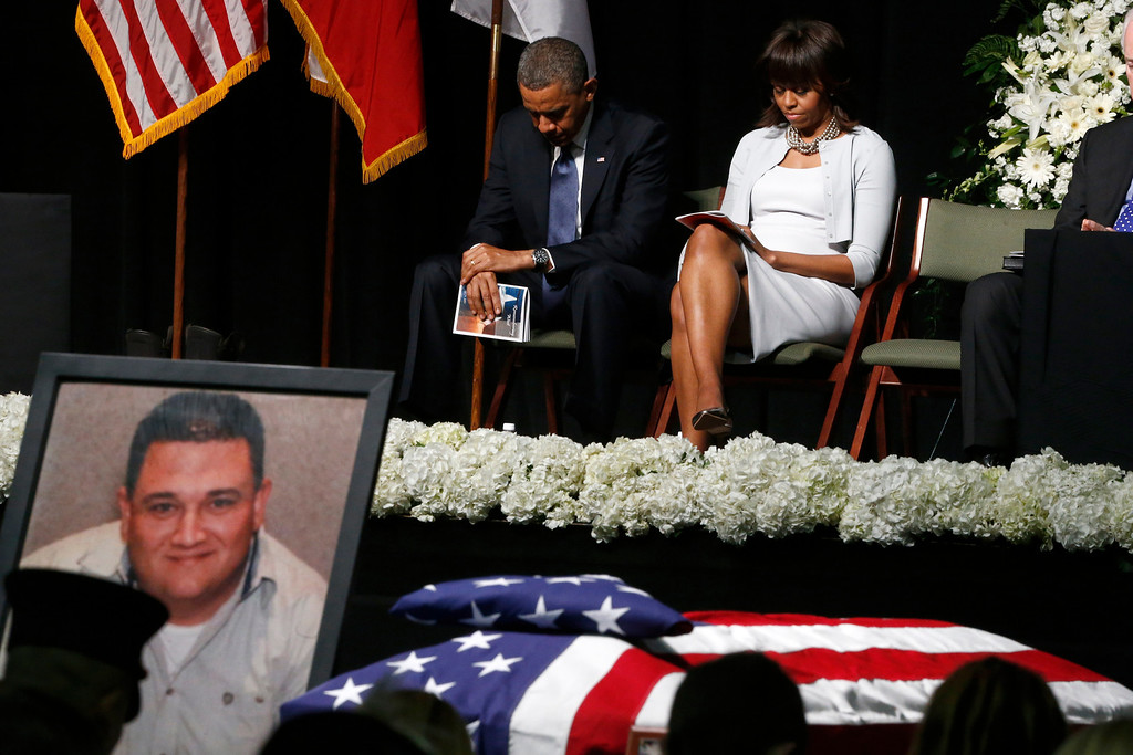 . President Barack Obama and first lady Michelle Obama bow their heads behind a photo of volunteer firefighter Capt. Cyrus Adam Reed, who was killed, as they attend the memorial for victims of the fertilizer plant explosion in West, Texas, Thursday, April 25, 2013, at Baylor University in Waco,Texas. (AP Photo/Charles Dharapak)