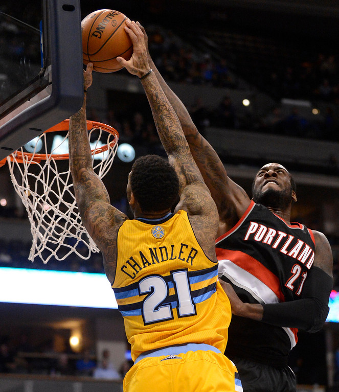 . Portland Trail Blazers center J.J. Hickson (21) blocks a shot by Denver Nuggets shooting guard Wilson Chandler (21) during the first quarter  Tuesday, January 15, 2013, at Pepsi Center. John Leyba, The Denver Post