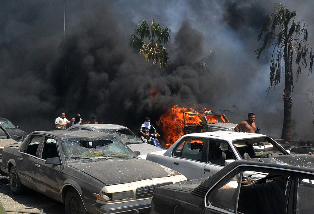 . Lebanese men run between burning cars at the site of an explosion outside a mosque in the Northern city of Tripoli, Lebanon, Friday Aug. 23, 2013.  (AP Photo)