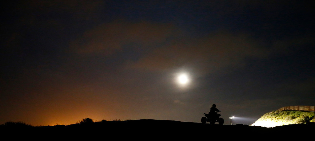 . The moon rises above a U.S. Customs and Border Patrol agent as he patrols along the international border between Mexico and the United States near San Diego, California, March 26, 2013. Picture taken March 26, 2013. REUTERS/Mike Blake