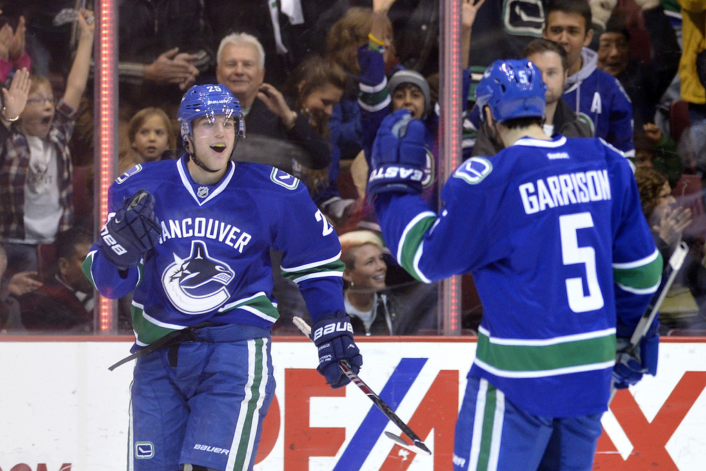 . Mike Santorelli #25 of the Vancouver Canucks celebrates with Jason Garrison #5 after scoring against the Colorado Avalanche during the first period in NHL action on December 08, 2012 at Rogers Arena in Vancouver, British Columbia, Canada.  (Photo by Rich Lam/Getty Images)