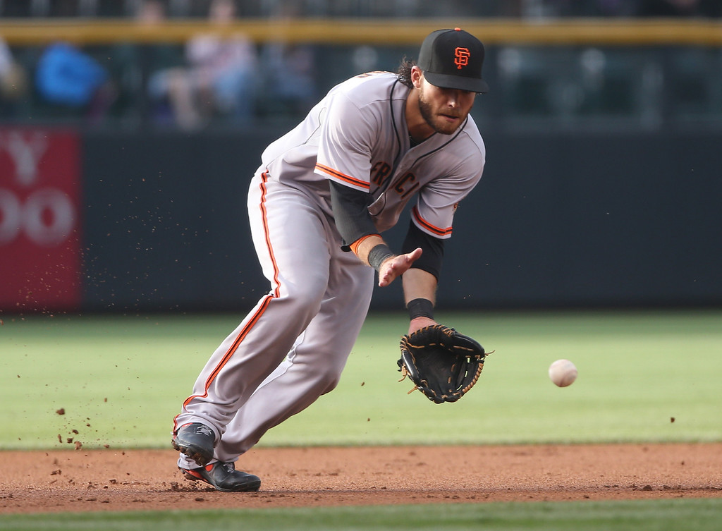 . San Francisco Giants shortstop Brandon Crawford fields ground ball off the bat of Colorado Rockies\' Troy Tulowitzki in the first inning of a baseball game in Denver on Wednesday, May 21, 2014. (AP Photo/David Zalubowski)