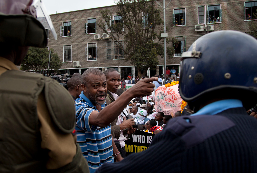 . A Kenyan demonstrator shout  slogans outside parliament  as riot police watch in Nairobi, Kenya, Tuesday, June 11, 2013.  Protesters gathered outside Kenya�s parliament building to pile pressure on the country�s legislators to drop demands for a salary increment. About 500 people carrying placards and banners marched through the Nairobi\'s city center and staged a sit in at the entrance legislators use to enter parliament. (AP Photo/Sayyid Azim)