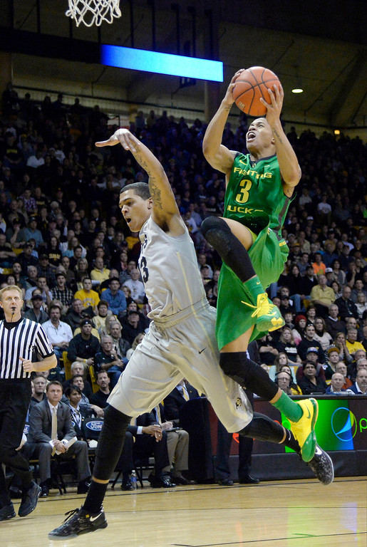 . Oregon Ducks guard Joseph Young (3) flies past Colorado Buffaloes forward Dustin Thomas (13) for a basket during the first half January 5, 2014 at Coors Events Center. (Photo by John Leyba/The Denver Post)
