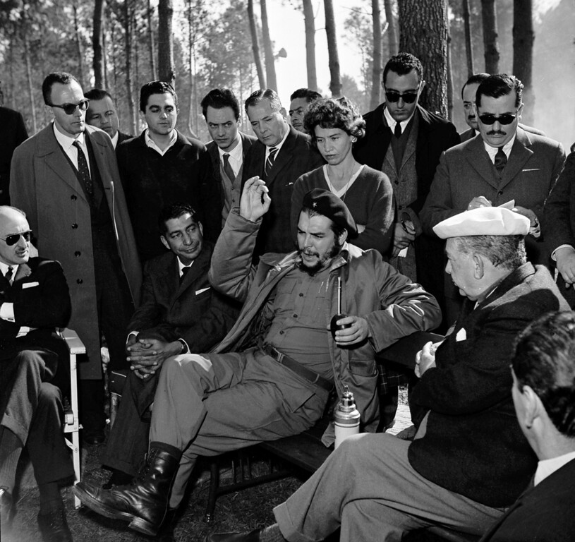 """. Cuban Industry Minister Ernesto \""""Che\"""" Guevara holds a mate (tea) gourd in one hand while gesturing with the other during a visit with Uruguay\'s President Victor Haedo, right, at Haedo\'s summer home in Punta del Este, Uruguay, Aug. 7, 1961. Guevara is here for the Inter-American Economic and Social Conference.  (AP Photo)"""