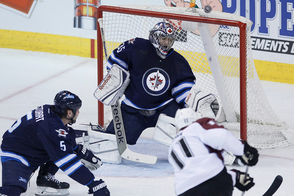 . Colorado Avalanche\'s Jamie McGinn (11) rips the puck past Winnipeg Jets\' goaltender Al Montoya (35) and off the crossbar as Jets\' Mark Stuart (5) helps defend during the first period of an NHL hockey game Wednesday, March 19, 2014, in Winnipeg, Manitoba. (AP Photo/The Canadian Press, John Woods)