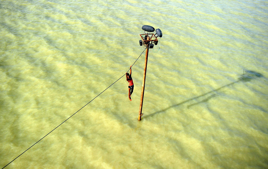. An Indian youth dangles from a power line before diving into the floodwaters of an overflowing Ganges river in Allahabad on August 6, 2013. The monsoon, which covers the subcontinent from June to September and usually brings flooding, accounts for about 80 percent of India\'s annual rainfall. Sanjay Kanojia/AFP/Getty Images