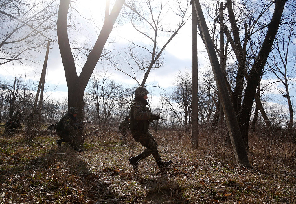 . Ukrainian border guards run to take their positions during training at a military camp in the village of Alekseyevka on the Ukrainian-Russian border, eastern Ukraine, Friday, March 21, 2014. (AP Photo/Sergei Grits)