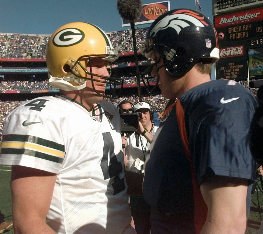 . Super Bowl XXXII quarterbacks Brett Favre, left, of the Green Bay Packers, and John Elway, of the Denver Broncos, meet on the field during warm-ups at Qualcomm Stadium Sunday, Jan. 25, 1998, in San Diego. (AP Photo/Dave Martin)