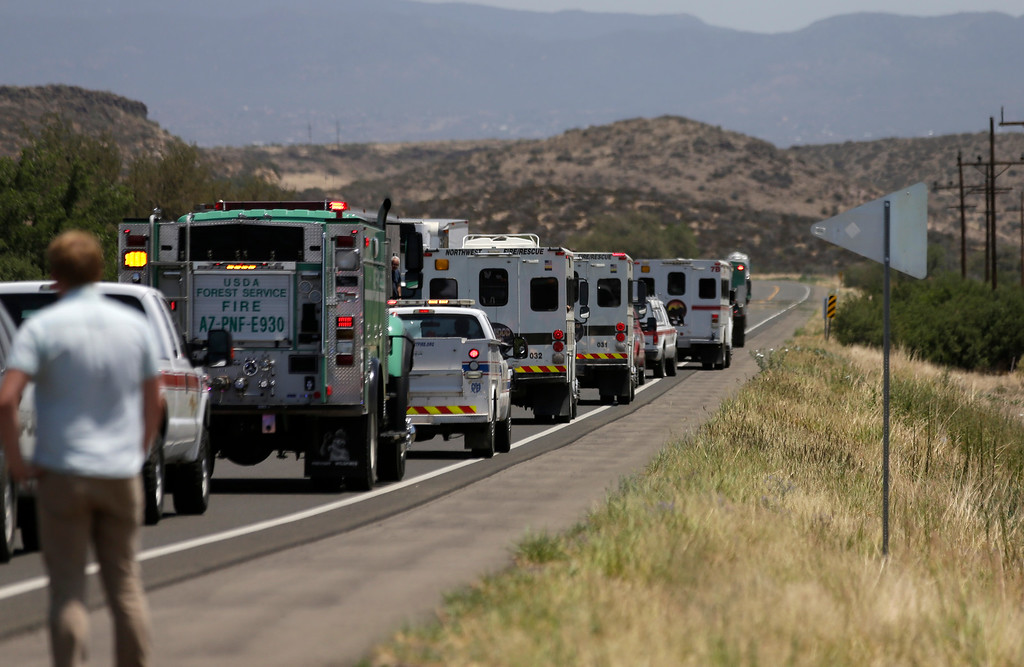 . A procession of the vehicles left by the 19 elite Granite Mountain Hotshot crew members killed over the weekend are removed from the fire area near Yarnell, Ariz., Wednesday, July 3, 2013. Violent wind gusts on Sunday turned a small, lightning-ignited forest fire in the town into an out-of-control wildfire that left no escape for the team of Hotshots. (AP Photo/Chris Carlson)